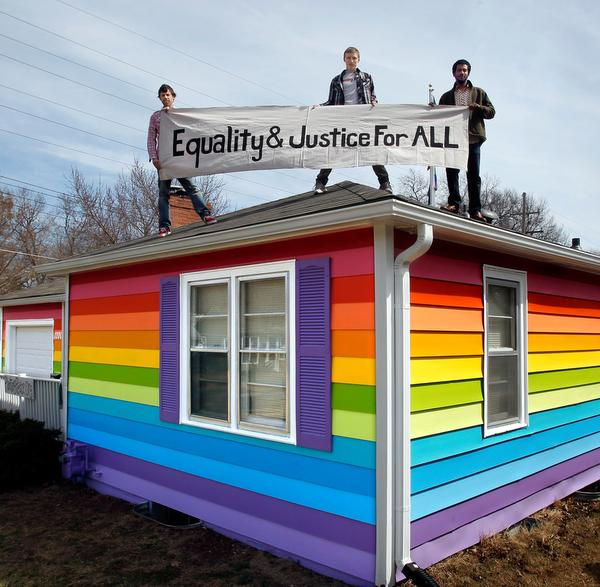 The non-profit group Planting Peace has bought a house across the street from the Westboro Baptist Church in Topeka and has painted the home a rainbow of colors. The group's co-founder, Aaron Jackson (from left), along with Davis Hammet and Robert Gisser, held one of their banners on Tuesday, April 2, 2013.   20130402